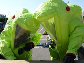 A Team Wearing Protective Clothing Assessing The Source Of A Leak Involving An Acid